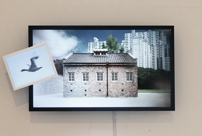 """Guem MinJeong, """"The Wind-Up Bird Chronicle_Prison for Woman"""", 2014, 2 LED monitor, Mixed Media, 65 x 150 x 15 cm."""